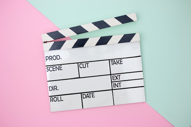 Clapper board on green and pink paster background