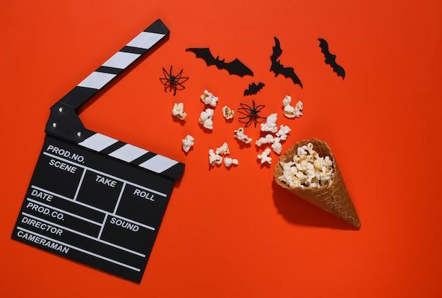 カチンコ、装飾的なコウモリとクモのアイスクリームワッフルコーン、オレンジ色の明るい背景のポップコーン。上面図。怖い映画。フラットレイハロウィーン構成