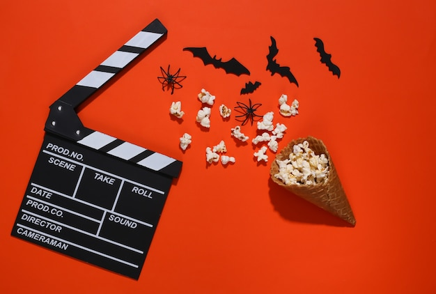 Clapper board, ice cream waffle cones with decorative bats and spiders, popcorn on orange bright background. top view. scary movie. flat lay halloween composition