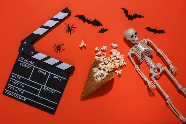 Clapper board, ice cream waffle cones with popcorn, decorative bats and spiders, skeleton on orange bright background. top view. scary movie. flat lay halloween composition