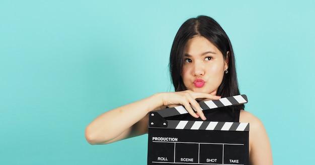 Доска с хлопушкой или хлопушка для кино в руке девочки-подростка или женщины. ее используют в производстве видео, кино, киноиндустрии на зеленом или синем фоне тиффани. она носит черное платье