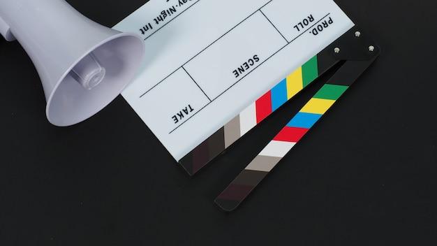 Доска с хлопушкой или киношифер и маска для лица, магафон на черном фоне. его используют в видеопроизводстве и киноиндустрии.