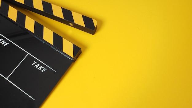 Доска с хлопушкой или сланец фильма с черным и желтым цветом и рулон пленки на желтом фоне. используется в видео-производстве и киноиндустрии.