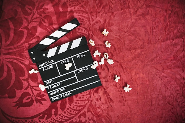 Clapper board and popcorn on velvet cloth