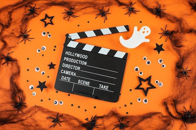 Clapper board in spider webs spiders ghost eyes on orange background