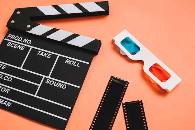 Clapperboard next to 3d glasses and film reels