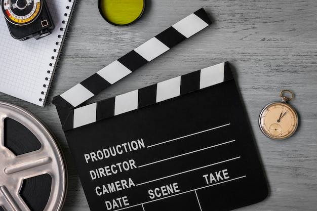 カチンコ、フィルムのロール、そしてテーブルの上の時計