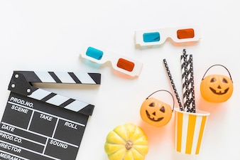 Clapperboard and 3D glasses near Halloween party stuff