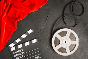 Clapperboard and bobbin near red cloth