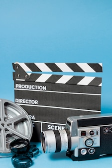 Clapperboard; camcorder camera; film reel and film stripes on blue backdrop
