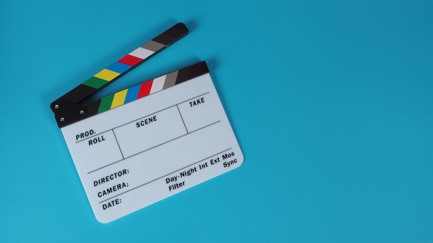 Clapperboard or movie slate on blue background.