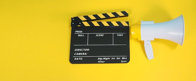 노란색과 검은색의 클래퍼보드 또는 영화 클래퍼 보드와 노란색 배경에 격리된 메가폰은 영화, 영화 및 비디오 제작에 사용됩니다.