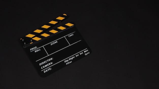 黒の背景にカチンコや映画のスレート。ビデオ制作や映画業界で使用されます。