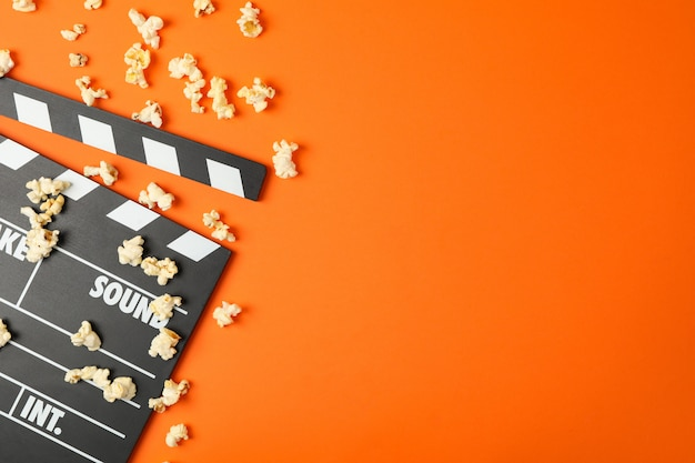 Clapperboard and popcorn on orange. food for watching cinema