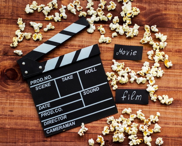 Clapperboard and popcorn on wooden table