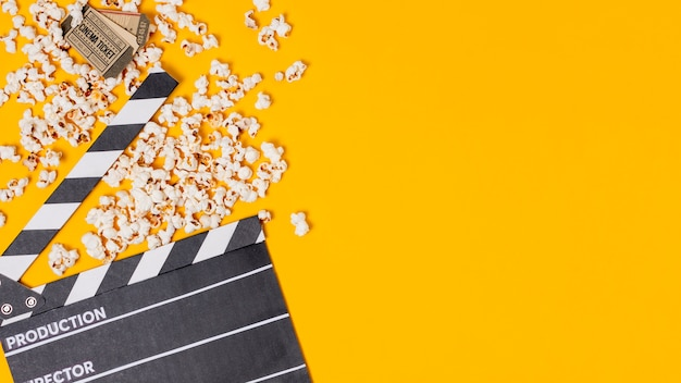 Clapperboard; popcorns and cinema tickets on yellow background