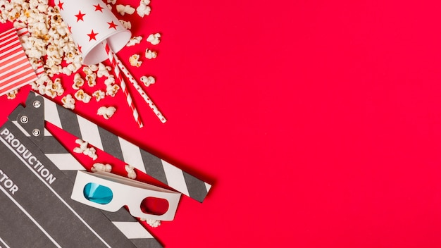 Clapperboard; popcorns and takeaway glass with drinking straws and popcorns on red background