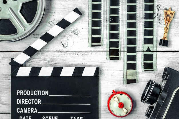 Clapperboard, reel, film and old movie camera