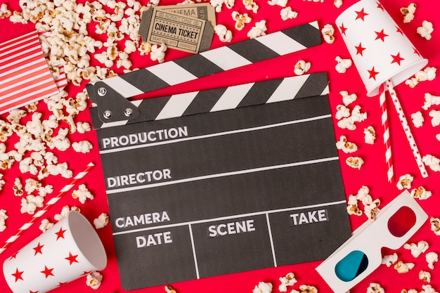 Clapperboard surrounded with popcorns; cinema tickets; takeaway glass; drinking straws and sunglasses on red backdrop