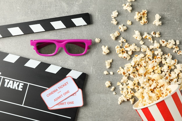 Clapperboard, tickets, 3d glasses and bucket with popcorn on grey background, top view