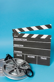 Clapperboard with film reel and film stripes against blue backdrop