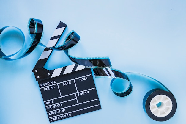 Clapperboard with filmstrip on blue