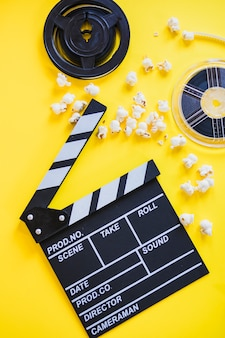 Clapperboard with popcorn and reels