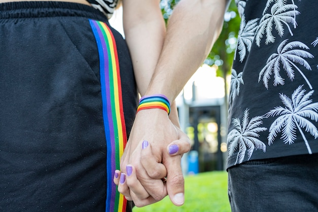 Clasped hands on natural background with lgbt bracelet