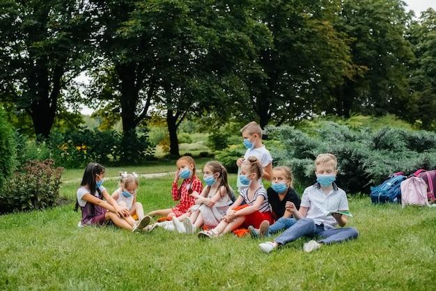 マスクされた学童のクラスは、流行中に屋外トレーニングに従事しています