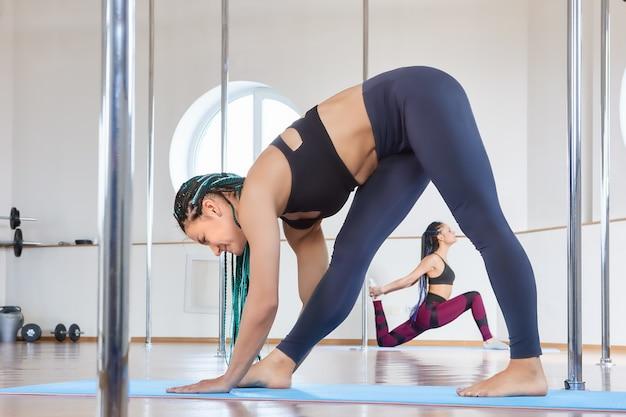 Занятия в студии pole dance, студенты делают упражнения на гибкость и растяжку.