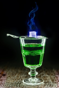 Classic absinthe cup with metal spoon and sugar melting in blue flame