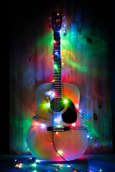 Classic acoustic guitar in christmas holiday lights in memory of music