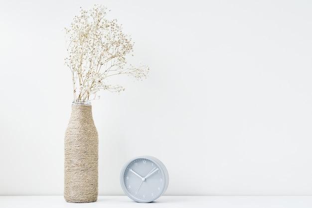 Классический будильник и цветочная ветка в вазе