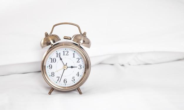 Classic alarm clock on bed.