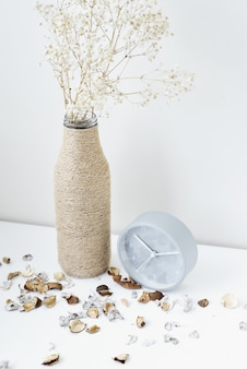 Classic alarm clock, flower branch and petals on a white table. cozy winter or autumn