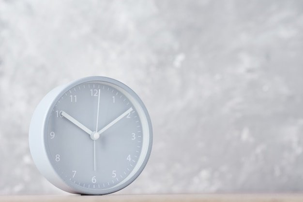 Classic alarm clock on a gray surface with copy space