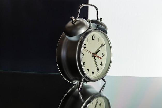 표면에 반사와 검은 색과 흰색 배경에 클래식 알람 시계. 광고 및 디자인에 대한 개념. 확대.
