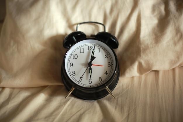 ベッドの上で朝6時を示す古典的な目覚まし時計