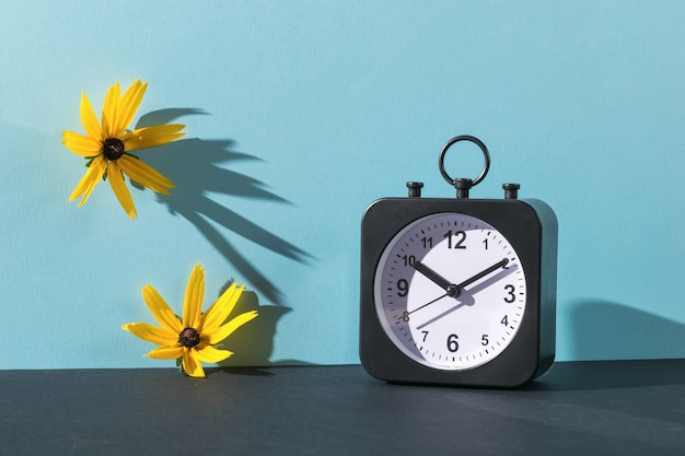 Classic alarm clock and two flowers in bright light on a blue background. crassic dial.