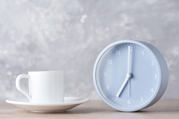 Classic alarm clock and white coffee cup on a gray