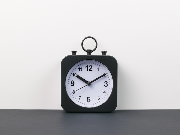 Classic alarm clock with hands on a black and gray background. crassic dial.