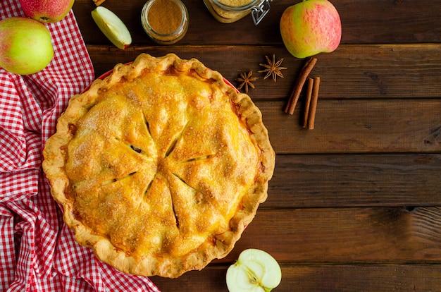Классический американский яблочный пирог с корицей на темном деревянном фоне. деревенский стиль. вид сверху, копия пространства.