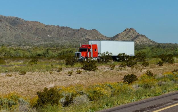 산 바위를 따라 도로에서 운전하는 평평한 침대 세미 트레일러로 운반되는 클래식 미국 대형 장비 세미 트럭