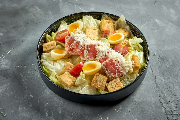 A classic american dish - caesar salad with salmon, croutons, parmesan and tomatoes in a black plate on a gray surface