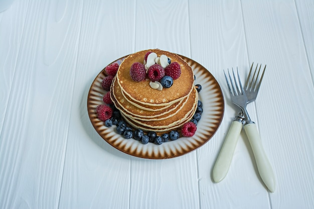 Classic american pancakes with fresh berry on a blue wooden background. pancakes with fruit. summer homemade breakfast.