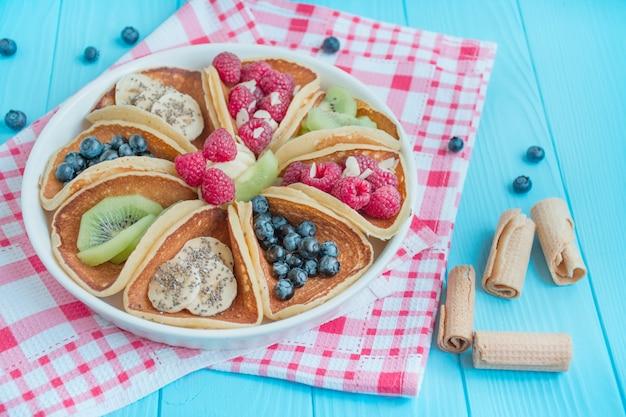 青い木製の背景に新鮮なベリーと古典的なアメリカのパンケーキ。フルーツのパンケーキ。夏の自家製朝食。コピースペース。食べ物を用意します。テーブル背景メニュー。