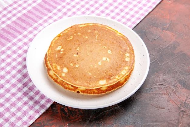 Pancake saporiti americani classici su un tovagliolo spogliato rosa sull'immagine di riserva di colore misto