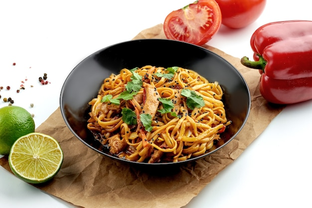 Classic asian street food - udon wok noodles with chicken, vegetables in sweet and sour sauce, served in a black plate