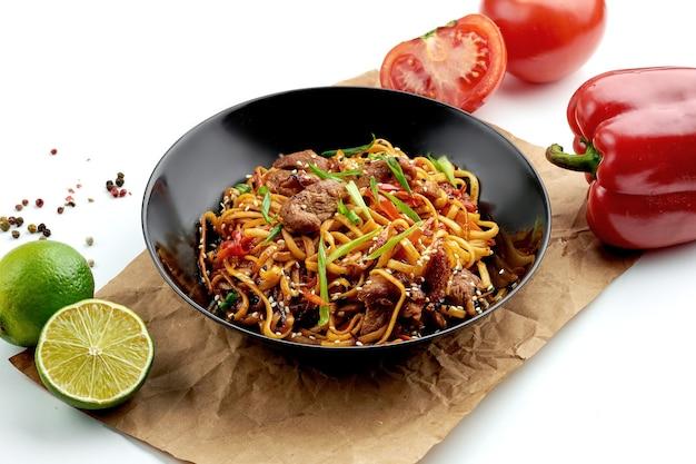 고전적인 아시아 길거리 음식-돼지 고기를 곁들인 우동 웍 국수, 새콤 달콤한 소스의 야채, 검은 접시에 제공