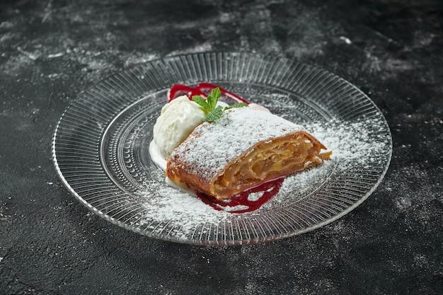 Классическая австрийская выпечка - штрудель из слоеного теста с яблоком, орехами и мороженым на темном столе. крупным планом, выборочный фокус